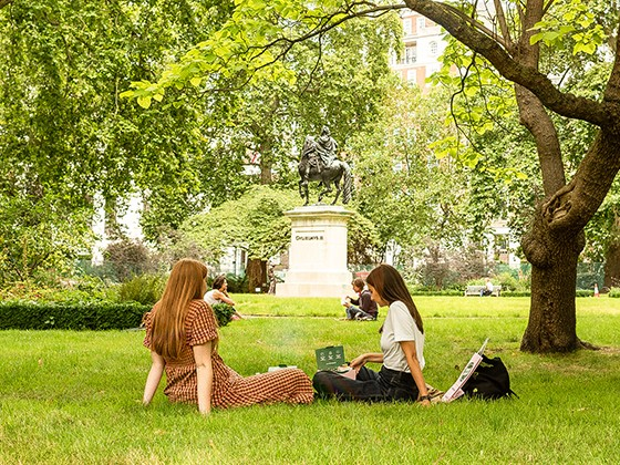 Two women having a picnic on the grass in St James's Square